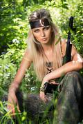 young woman holding an automatic assault rifle - stock photo