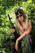 Young woman holding an automatic assault rifle Stock Photos