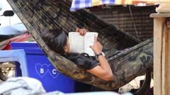 Asian adult woman reading book while she's resting in her hammock Stock Footage
