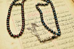 Muslim rosary beads on the Holy Quran - stock photo