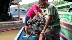 Men preparing old boat motor to navigate river, Burma Stock Footage