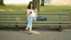 Texting a message in the park Stock Footage