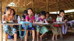 Group of Asian children sitting and writing at improvised school, Burma Stock Footage