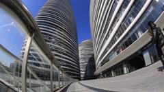People walking among office buildings under blue sky, sunny day in Beijing Stock Footage
