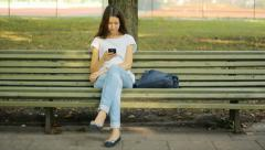Girl using a cell phone, park Stock Footage