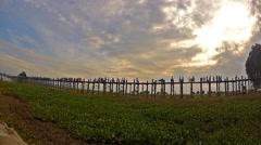 People walk on famous U Bein bridge at sunset in Amarapura, Burma (Myanmar) Stock Footage