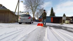 Man scraping snow with a snow scraper Stock Footage