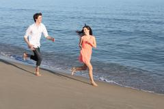 Couple of teenagers running and flirting on the beach - stock photo