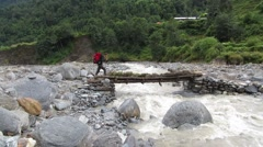 Hiker passing across a wooden bridge in the Himalayas Stock Footage