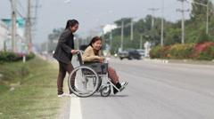 Senior woman using a wheelchair cross street (sound quality) Stock Footage