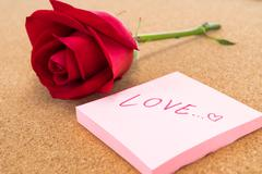 "Single red rose with post it with word ""love"", corkboard background - stock photo"