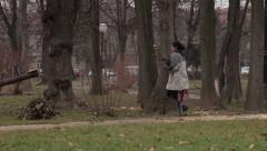 Female gypsy collecting branches for heating in park. Pan left. Baby in stroller Stock Footage