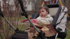 Cute baby in the blue dirty stroller waiting for parents in the park. Unicef. Stock Footage