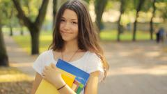 Girl smiling, looking at camera, books Stock Footage