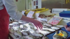 Fishmonger arranges market stall. Stock Footage