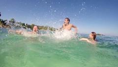 SLOW MOTION beach water splashing: young teens having summer beach party fun. Stock Footage
