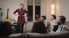 Young woman playing charades with friends at home Stock Footage