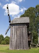 Old wooden windmill on background of blue sky Stock Photos