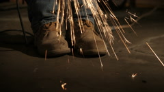 Sparks flying all around work boots. Stock Footage