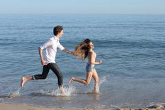 Couple chasing and running on the beach - stock photo
