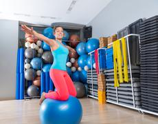Girl at gym swiss ball knee balance drill exercise Stock Photos