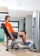 Hip abduction blond man exercise at gym closing - stock photo