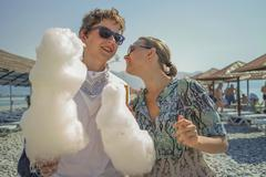 Boy and girl eating cotton candy at the beach Kuvituskuvat