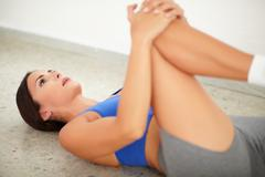 Brunette female exercising pilates for good posture and wellbeing at gym - stock photo