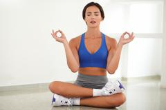Pretty woman doing relaxation exercise while smiling with closed eyes - stock photo