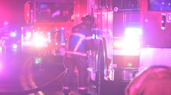 Firefighter breaking down fire hose Stock Footage