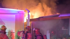 Mobile home fire lots of smoke flames and firefighters Stock Footage