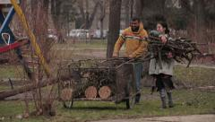 Poor husband and wife gypsy putting wood and branches for heating in trolley. Stock Footage