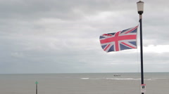 Union Flag (of Great Britain) On a Seaside Beach Lamppost Flying in the Wind - stock footage