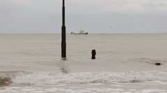 Boat or Ship in the Background of waves washing posts in the sea at Teignmouth Stock Footage