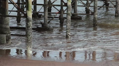 Gentle Sea Waves Wash Pillars of the Base of Teignmouth Pier on Sand Beach Stock Footage