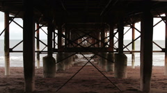 Abstract Grunge Wide Shot Through Rusty Pillar Supports of Pier Metal Structure Stock Footage