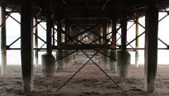Abstract Grunge Tilt Shot Through Rusty Pillar Supports of Teignmouth Pier Stock Footage