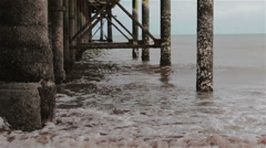 Gentle Sea Waves Wash Base Pillars of Teignmouth Pier on Sand Beach Stock Footage