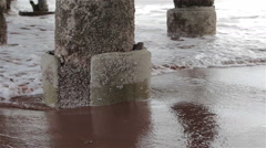 Gentle Sea Waves Wash Concrete Pillars at Base of Pier on Teignmouth Sand Beach Stock Footage