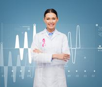 Smiling female doctor with cancer awareness ribbon Stock Photos