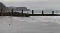 Gentle Sea Washes Against Sand of Teignmouth Beach & Wave Breakers Cloudy Day Stock Footage