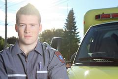 Paramedic employee with ambulance in the background - stock photo