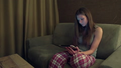 Young girl sitting on sofa in the evening and using tablet computer slo-mo Stock Footage