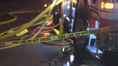 Fire hose coming of a fire truck  and police tape Stock Footage