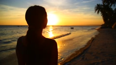 Young girl looks at the sea at sunset Stock Footage