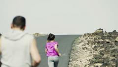Young people jogging up through road  HD Stock Footage