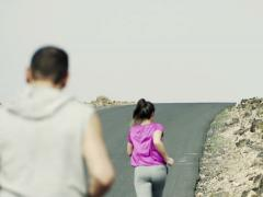 Young people jogging up through road NTSC Stock Footage