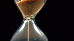 Sand Flowing Through an Hourglass on black background. 4K Stock Footage