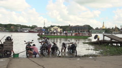 Pathein, Men wash their motorbikes in the river Stock Footage