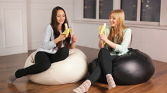 Two girls sitting at bag chairs peel and eat big bananas - stock footage
